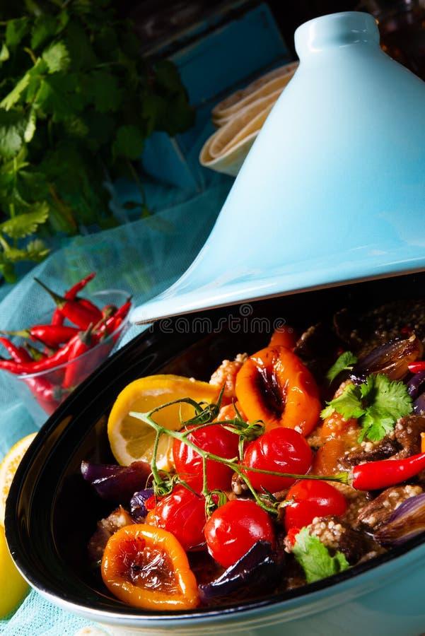 Smakligt kryddigt nötkött med olika grönsaker som lagas mat i tagine royaltyfri foto