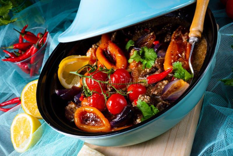 Smakligt kryddigt nötkött med olika grönsaker som lagas mat i tagine royaltyfria bilder