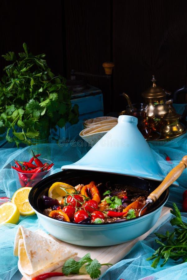 Smakligt kryddigt nötkött med olika grönsaker som lagas mat i tagine arkivbild