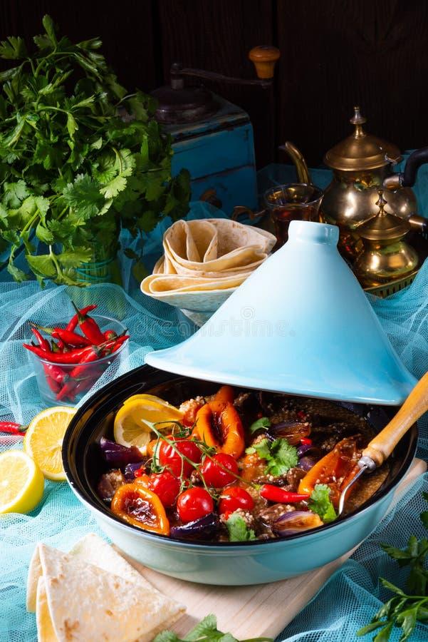 Smakligt kryddigt nötkött med olika grönsaker som lagas mat i tagine royaltyfri bild