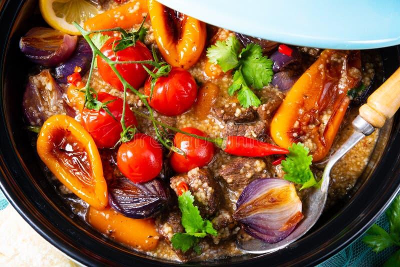 Smakligt kryddigt nötkött med olika grönsaker som lagas mat i tagine fotografering för bildbyråer