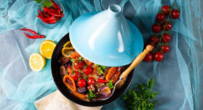 Smakligt kryddigt nötkött med olika grönsaker som lagas mat i tagine royaltyfri fotografi