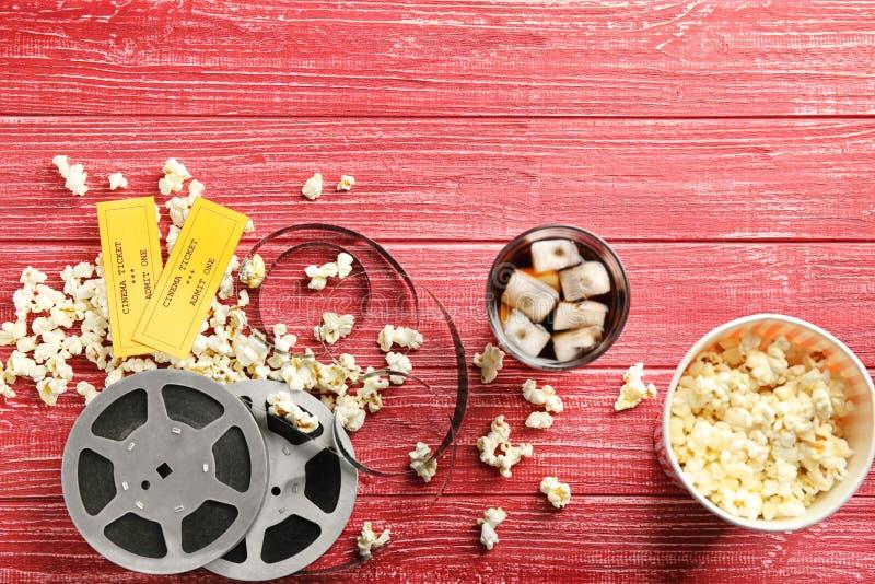 Smakligt popcorn, biljetter och filmen reel på röd bakgrund royaltyfri fotografi