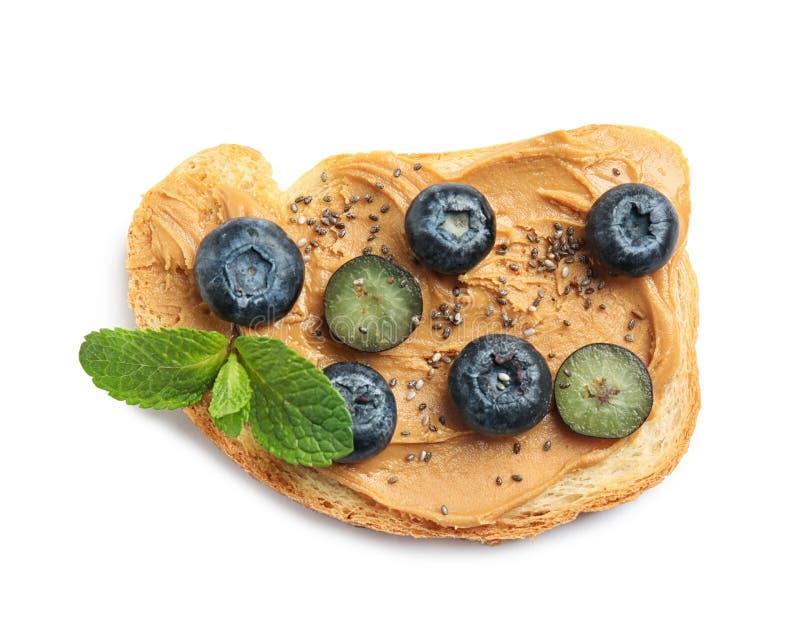 Smakligt rostat bröd med blåbär, jordnötsmör och chiafrö på den vita bästa sikten royaltyfria bilder