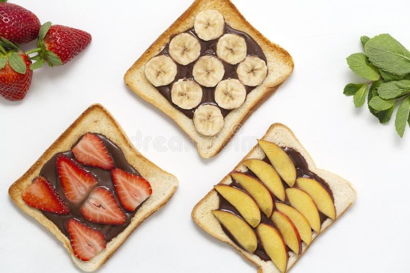 Smakligt rostat brödbröd med den chokladdeg, bananen, jordgubben och persikan på vit bakgrund arkivbild