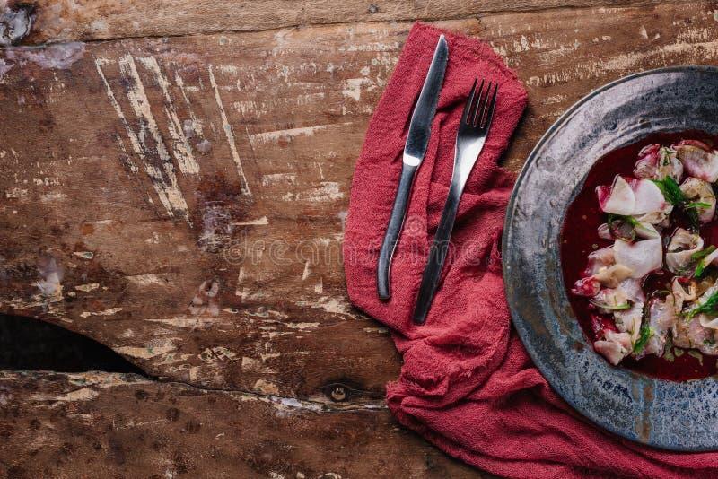 smakosz Ceviche z dorado w talerzu, rozwidleniu i nożu na drewnianym, obraz royalty free