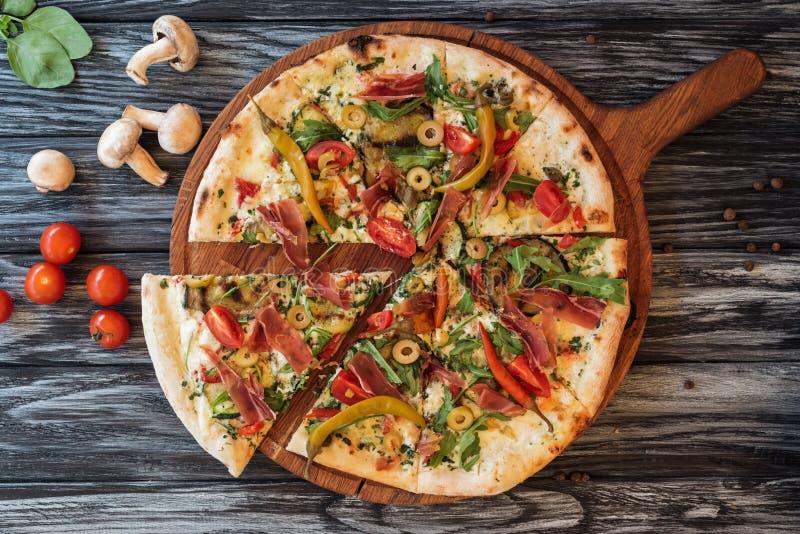 smakosz pokrajać pizzę z warzywami i mięsem na drewnianym obrazy royalty free