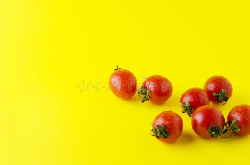 Smakowici świezi czereśniowi pomidory z kroplami woda na żółtym jaskrawym stole zdjęcia royalty free