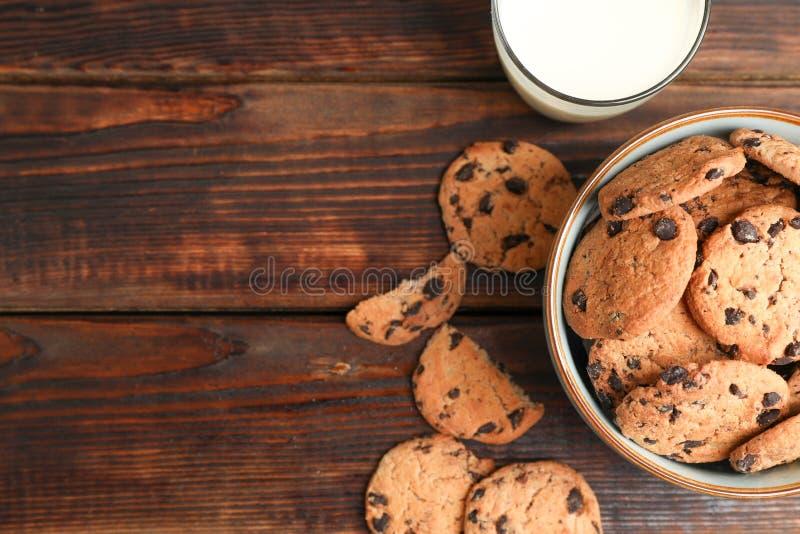 Smakowici czekoladowego układu scalonego ciastka i szkło mleko na drewnianym stole, odgórny widok fotografia stock