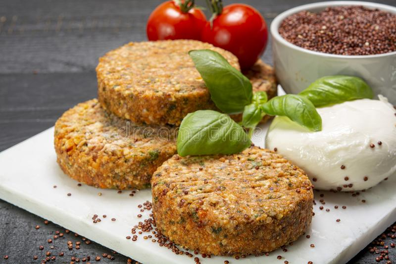 Smakowici jarscy hamburgery robić od zdrowego quinoa, basila, pomidorów i mozzarella sera, fotografia stock