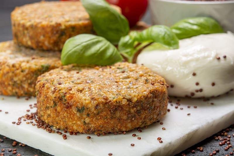 Smakowici jarscy hamburgery robić od zdrowego quinoa, basila, pomidorów i mozzarella sera, zdjęcie stock