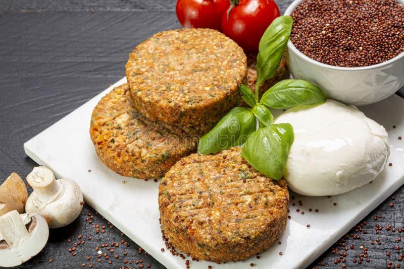 Smakowici jarscy hamburgery robić od zdrowego quinoa, basila, pomidorów i mozzarella sera, obrazy royalty free