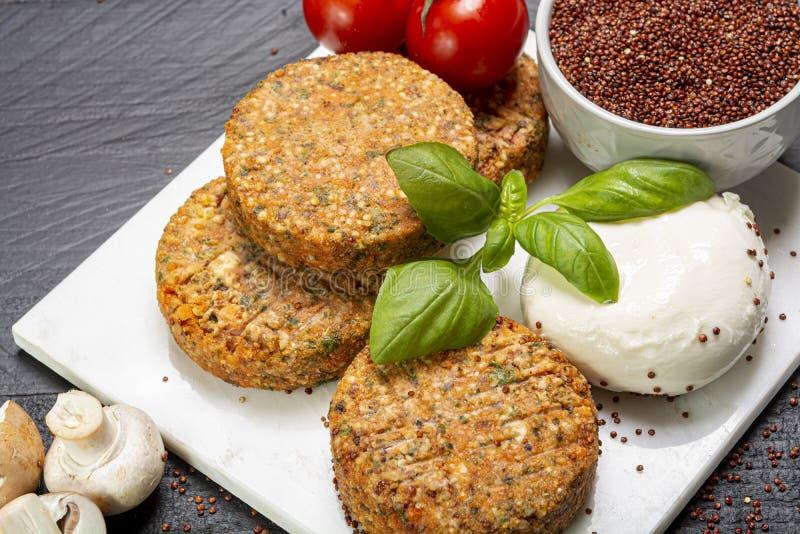 Smakowici jarscy hamburgery robić od zdrowego quinoa, basila, pomidorów i mozzarella sera, obraz royalty free