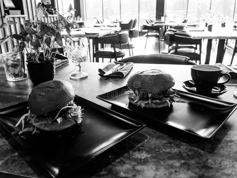Smakowici ogromni hamburgery w restauracyjnej kawiarni zdjęcie stock