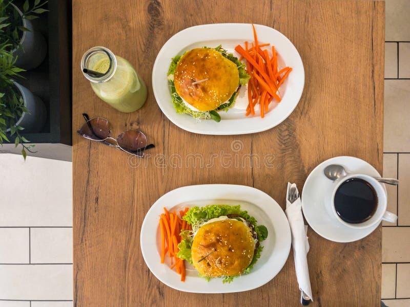Smakowici piec na grillu domowi robić hamburgery z wołowiną, marchewkami, serem, sałatą i kawą, koktajl na drewno stole obrazy stock