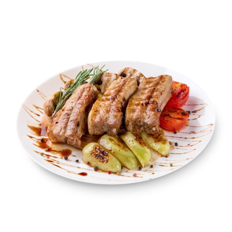 Smakowici piec na grillu ziobro z warzywami na talerzu, odosobnionym na białym tle zdjęcie royalty free