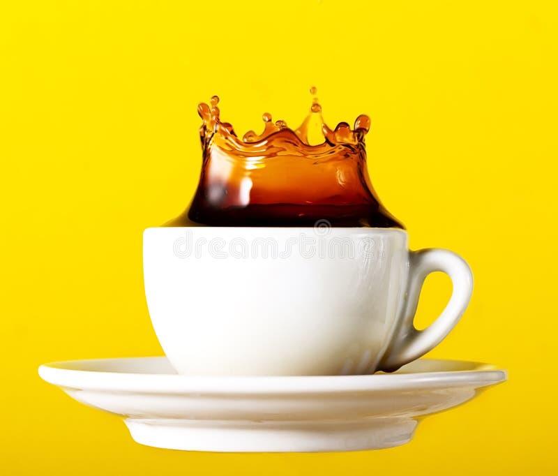 Smakowita świeża czarna kawa w filiżanki pluśnięcia koronie na żółtym wibrującym b obraz royalty free