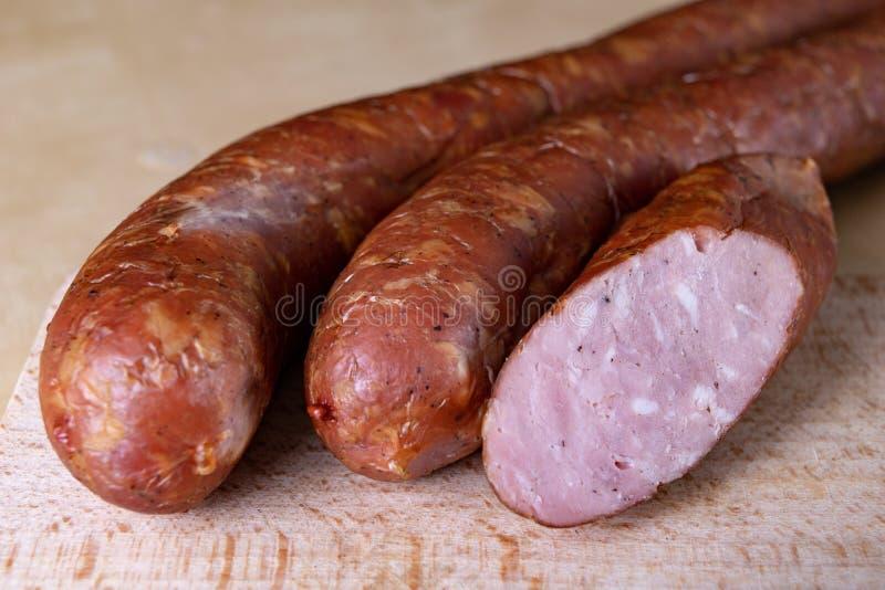 Smakowita, świeża kiełbasa, dymił na kuchennym stole Smakowici mięsa przygotowywający dla domowego świętowania zdjęcie stock