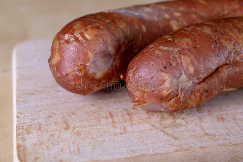 Smakowita, świeża kiełbasa, dymił na kuchennym stole Smakowici mięsa przygotowywający dla domowego świętowania zdjęcia royalty free