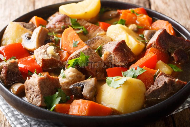 Smakowita g?sta gulasz wieprzowina z pieczarkami, grulami, marchewkami i pieprzu zbli?eniem na talerzu, horyzontalny obrazy stock