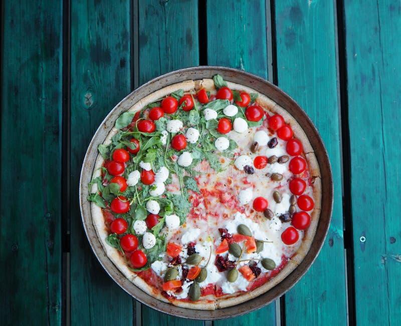 Smakowita jarska pizza z czereśniowymi pomidorami, oliwkami i sałatkowym właśnie piec, Zielony drewniany tło obraz royalty free