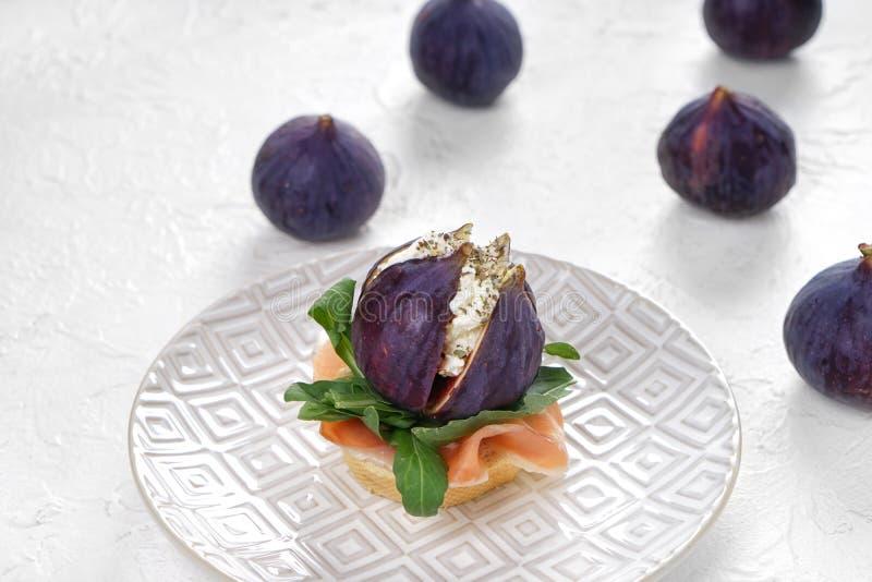 Smakowita kanapka z dojrzałą figą, kremowym serem i prosciutto na talerzu, obraz royalty free