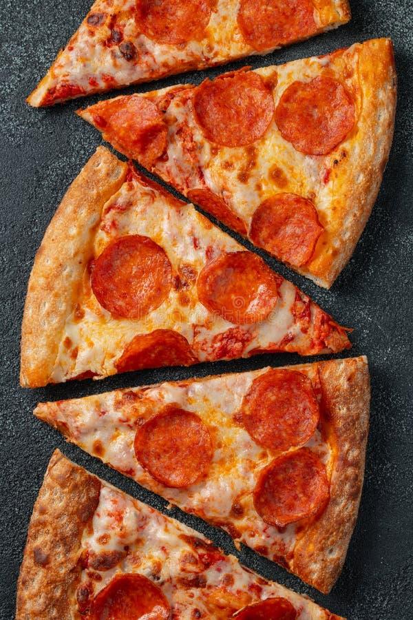 Smakowita pepperoni pizza i kulinarny składników pomidorów basil na czerni betonujemy tło Odgórny widok gorąca pepperoni pizza mi obraz stock