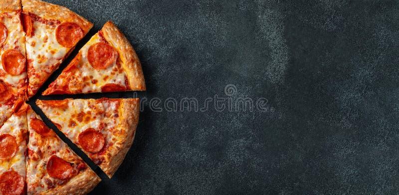 Smakowita pepperoni pizza i kulinarny składników pomidorów basil na czerni betonujemy tło Odgórny widok gorąca pepperoni pizza z zdjęcia stock
