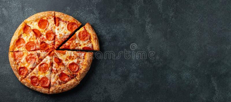 Smakowita pepperoni pizza i kulinarny składników pomidorów basil na czerni betonujemy tło Odgórny widok gorąca pepperoni pizza z obraz stock