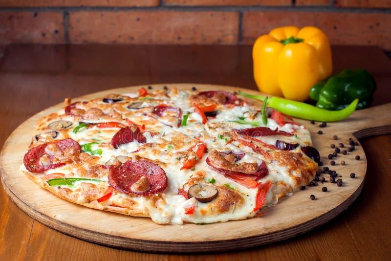 Smakowita Pepperoni pizza z salami szef kuchni poj?cia karmowa ?wie?a kuchni oleju oliwka nad dolewania restauraci sa?atk? zdjęcie stock