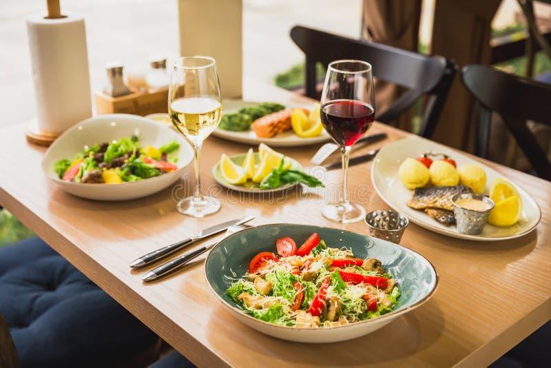 Smakowita sałatka z rybimi naczyniami i szkło wino Zdrowy jedzenie w kawiarni zdjęcie royalty free