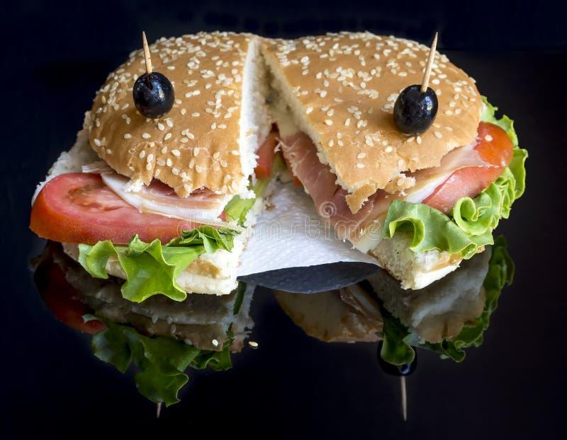Smakowita sezamowego ziarna kanapka faszerował z baleronem, świeżą sałatką, czerwonymi pomidorami i czarnymi oliwkami na czarnym  zdjęcia royalty free