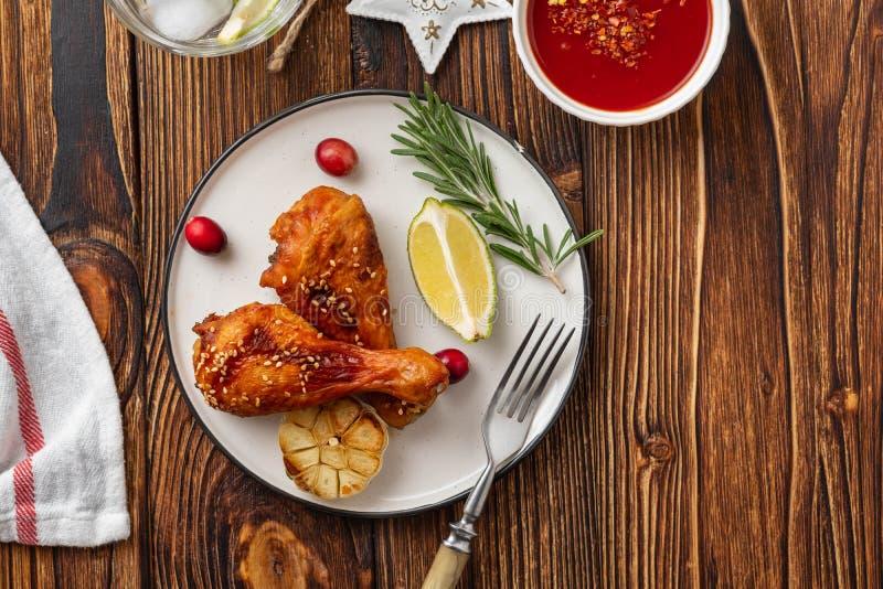 Smakowite apetyczne piec kurczak nogi słuzyć z pikantność, rozmarynami i cranberries na drewnianym tło stole, Boże Narodzenia fotografia stock