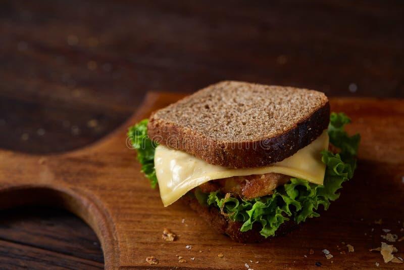Smakowite i świeże kanapki na tnącej desce nad ciemnym drewnianym tłem, zakończenie fotografia stock