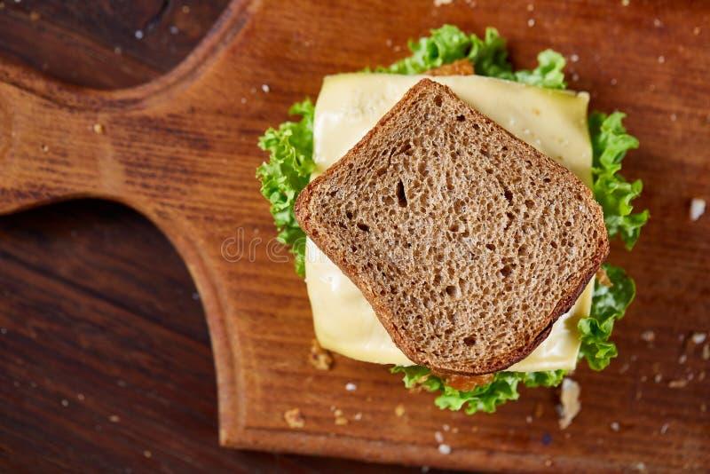 Smakowite i świeże kanapki na tnącej desce nad ciemnym drewnianym tłem, zakończenie zdjęcia stock