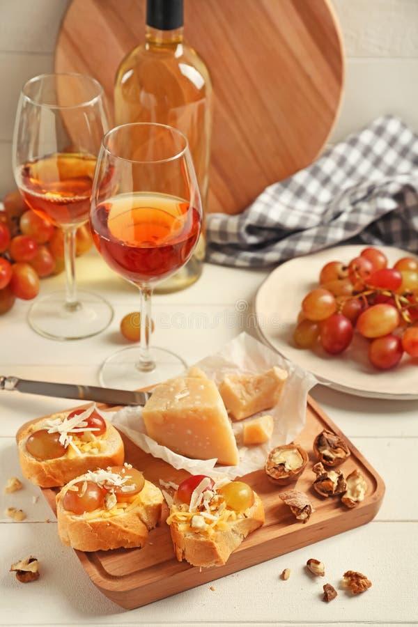Smakowite kanapki z serem, winogronem i dokrętkami na drewnianej desce, fotografia royalty free