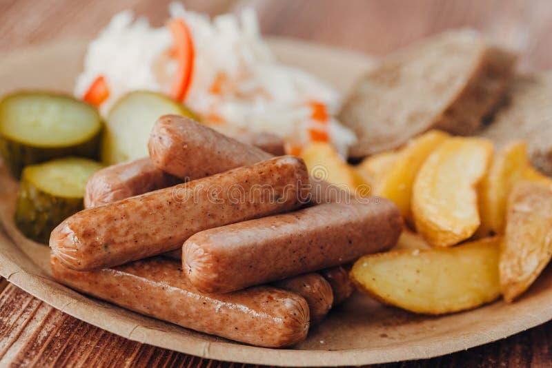 Smakowite kiełbasy z grulami, ogórkiem, kapustą i chlobe w papierowym talerzu na drewnianym stole smażącymi, zdjęcia stock