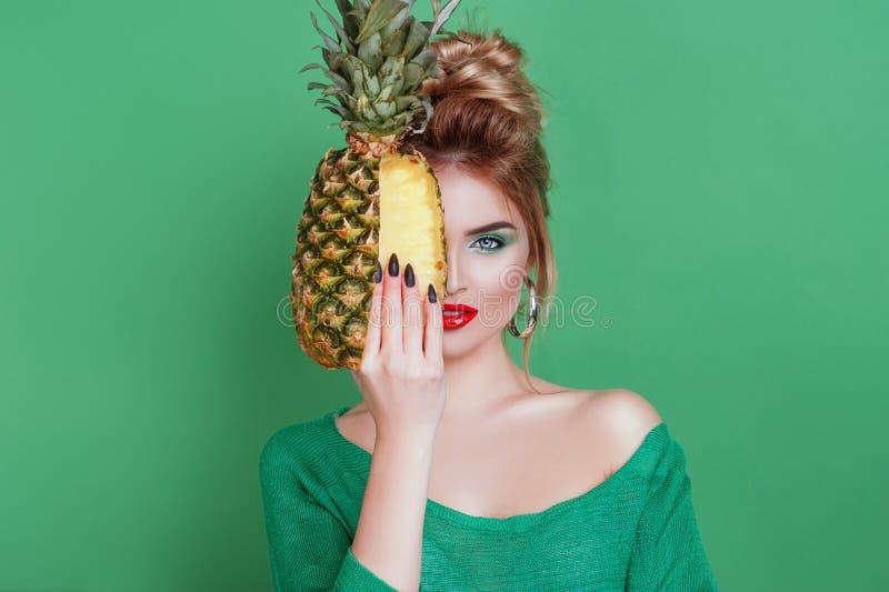 Smakowite tropikalne owoc! Atrakcyjna plciowa kobieta trzyma świeżego soczystego ananasa i patrzeje krzywka na odosobnionym z pię fotografia stock