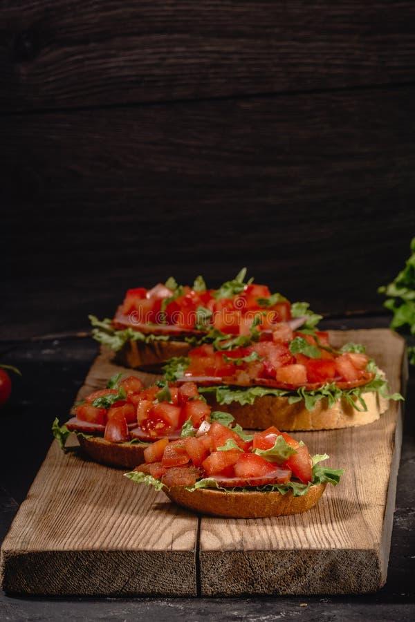 Smakowitego cząberu pomidorowe Włoskie zakąski lub bruschetta, na plasterkach wznoszący toast baguette garnirujący z sałatk zdjęcie stock