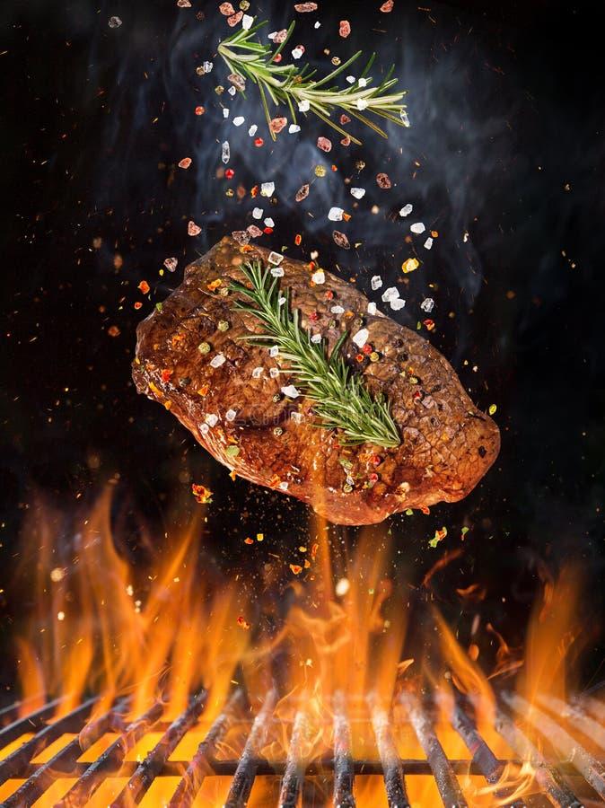 Smakowitego wołowina stku latania obsady żelaza above kratownica z pożarniczymi płomieniami zdjęcie stock