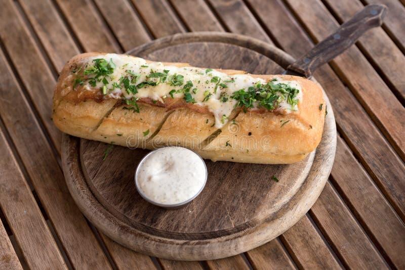 Smakowity chleb z czosnkiem, serem i ziele na drewnianym stole, zdjęcie royalty free