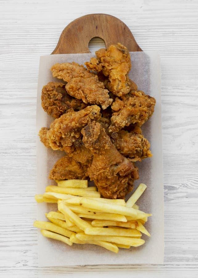 Smakowity fastfood: pieczonych kurczaków drumsticks, korzenni skrzydła, francuz smażą i kurczak składa na nieociosanej drewnianej zdjęcia stock