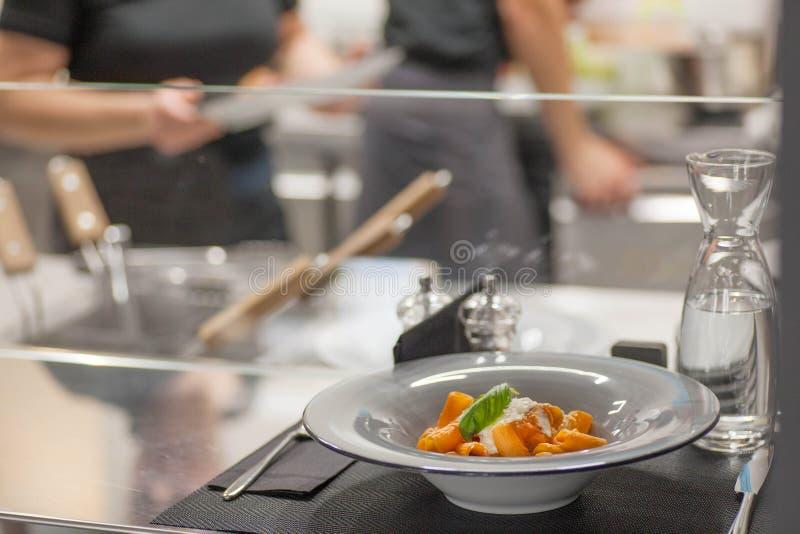 Smakowity makaron w pomidorowym kumberlandzie z basilem Popularny włoski jedzenie na stołowej pobliskiej otwartej kuchni nowożytn zdjęcie stock
