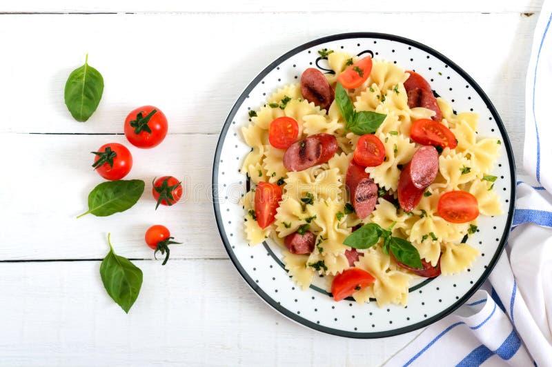 Smakowity makaronu farfalle z piec na grillu kiełbasami, świeżymi czereśniowymi pomidorami i basilem na talerzu na białym drewnia obraz royalty free
