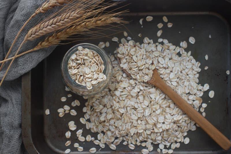Smakowity odżywczy oatmeal, szklany słój, drewniana łyżka i ucho kukurudza na ciemnym tle, odgórny widok zdjęcie stock