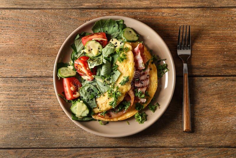 Smakowity omlet z bekonem i warzywami na talerzu zdjęcia stock