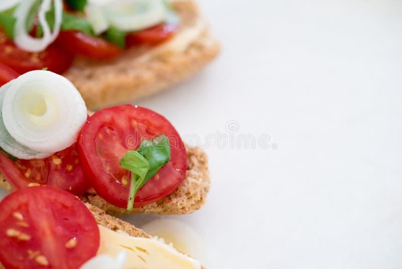 Smakowity palcowy jedzenie wiosen cebule i czereśniowy ser z basilem na piec bruschetta chlebie pomidorów i organicznie obrazy stock