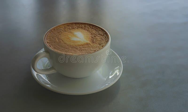 Smakowity pić, filiżanka dekorująca z serce wzorem na brązu mleku capuccino kawa spienia w białej ceramicznej filiżance na szaroś obraz stock