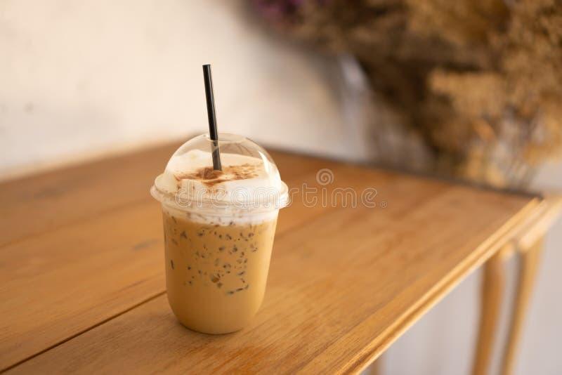 Smakowity pi?, fili?anka lodowa cappuccino kawa dekoruj?ca z bielu mlekiem spienia w wysokim plastikowym szkle na br?zu drewniany zdjęcie royalty free