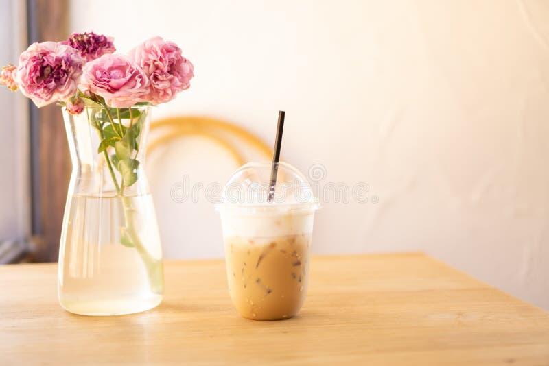 Smakowity pi?, fili?anka lodowa cappuccino kawa dekoruj?ca z bielu mlekiem spienia w wysokim plastikowym szkle na br?zu drewniany obrazy royalty free
